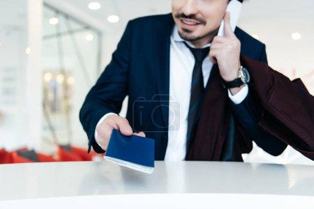 Photo pour Recadrée vue d'homme d'affaires en costume avec passeport parler sur smartphone en faisant check-in à l'hôtel - image libre de droit