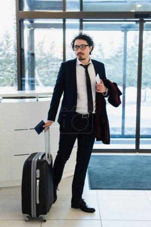 Photo pour Homme d'affaires avec le smartphone, passeport et voyage sac permanent à réception de l'hôtel - image libre de droit
