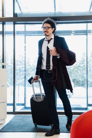 Photo pour Sourire d'homme d'affaires avec le smartphone, passeport et voyage sac dans le hall de l'hôtel - image libre de droit