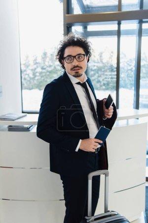 Photo pour Homme d'affaires avec le smartphone, des passeports et des bagages en attente pour le check-in à l'hôtel - image libre de droit