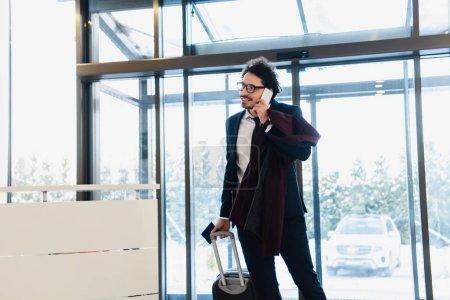 Photo pour Sourire d'homme d'affaires avec les passeports et bagages parler sur smartphone dans le hall de l'hôtel - image libre de droit
