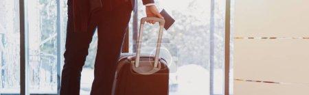 Photo pour Recadrée vue d'homme d'affaires avec des passeports et des bagages à venir à l'hôtel avec la lumière du soleil - image libre de droit