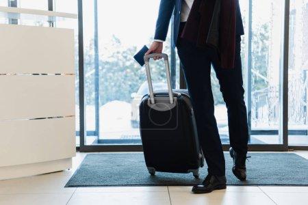 Photo pour Vue recadrée d'homme d'affaires avec passeport et voyage sac à venir à l'hôtel - image libre de droit