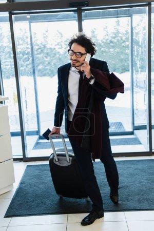 Foto de Sonriente hombre de negocios con pasaporte y viaje bolsa hablando en smartphone en el hall del hotel - Imagen libre de derechos