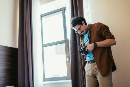 Photo pour Homme à lunettes appareil photo près de fenêtre dans la chambre d'hôtel en regardant souriant - image libre de droit