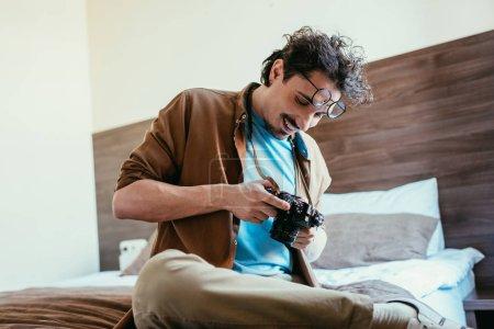 Photo pour Photographe à lunettes appareil photo dans la chambre d'hôtel en regardant - image libre de droit