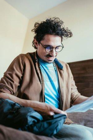 Photo pour Bel homme lisant le journal dans la chambre d'hôtel - image libre de droit