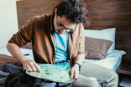 Photo for Male tourist in eyeglasses looking at map in hotel room - Royalty Free Image