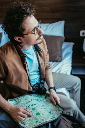 Photo pour Voyageur pensif avec appareil photo détenant la carte dans la chambre d'hôtel - image libre de droit