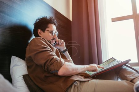 Photo for Tourist talking on smartphone while looking at map in hotel room - Royalty Free Image