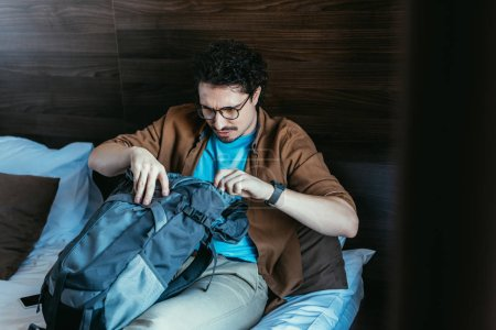 Photo for Male tourist looking into backpack in hotel room - Royalty Free Image