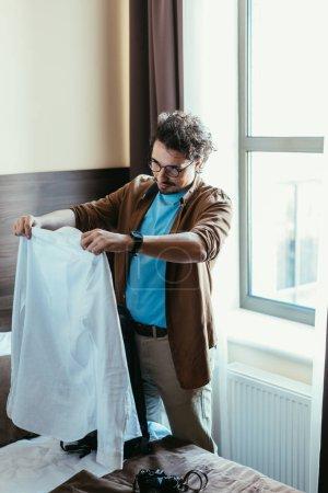 Photo pour Beau mâle touriste mettre chemise dans le sac à dos dans la chambre d'hôtel - image libre de droit