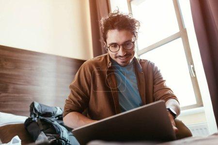 Photo pour Voyageur masculin souriant utilisant un ordinateur portable dans la chambre d'hôtel avec sac à dos - image libre de droit