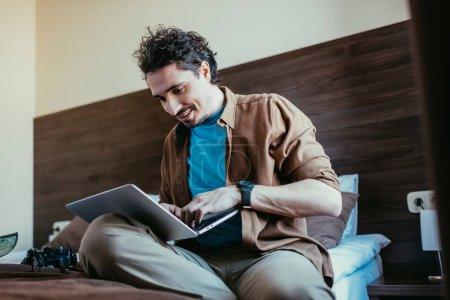 Photo pour Voyageur souriant en utilisant l'ordinateur portable dans la chambre d'hôtel avec l'appareil photo sur le lit - image libre de droit
