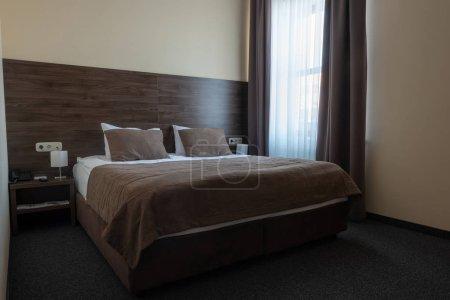 Foto de Interior de habitación de Hotel con ventana y cama marrón - Imagen libre de derechos
