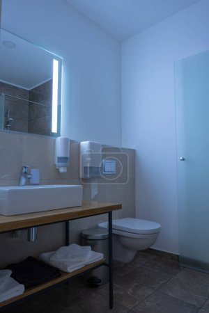 Photo for Hotel bathroom interior with sink, toilet, mirror and towels - Royalty Free Image