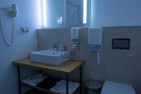 Foto de Baño con lavabo, WC, toallas y secador de pelo - Imagen libre de derechos