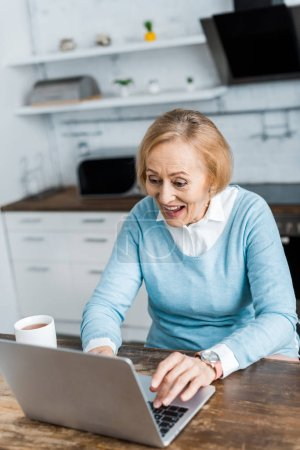 aufgeregte Seniorin sitzt mit Tasse Tee am Tisch und benutzt Laptop in der Küche