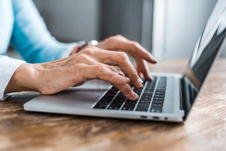 Photo pour Vue partielle de haute femme dactylographie sur ordinateur portable à la maison - image libre de droit