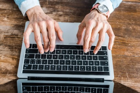 Photo for Top view of senior woman typing on laptop at home - Royalty Free Image