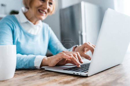 Photo for Selective focus of smiling senior woman typing on laptop at home - Royalty Free Image
