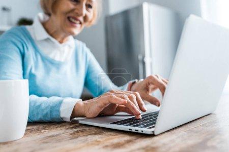 Photo pour Foyer sélectif de sourire femme âgée tapant sur ordinateur portable à la maison - image libre de droit
