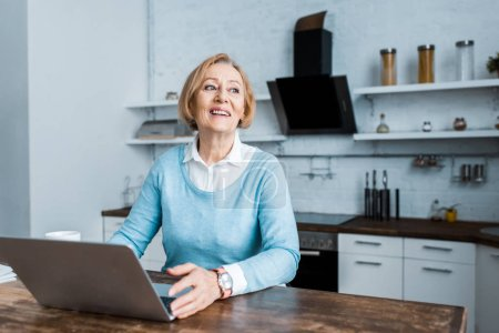 smiling senior woman in casual clothes sitting at table with laptop in kitchen