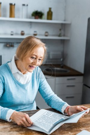 senior woman sitting and reading newspaper at home