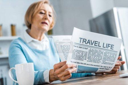mujer mayor sentada y leyendo el periódico de viaje en casa