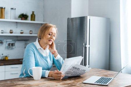 Photo pour Senior femme assise à table avec une tasse de café et ordinateur portable tout en lisant le journal à la cuisine - image libre de droit