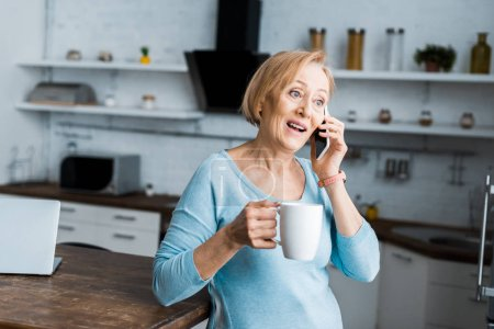 Photo for Surprised senior woman with cup of coffee talking on smartphone at home - Royalty Free Image