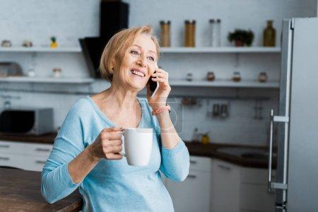 femme âgée souriante avec tasse de café parler sur smartphone à la maison