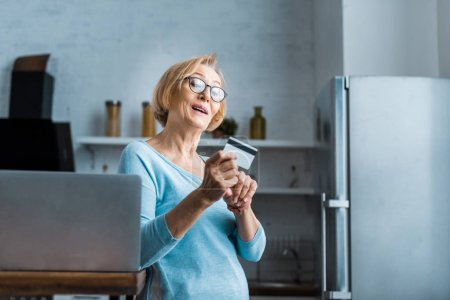surprised senior woman in glasses holding credit card near laptop at home with copy space