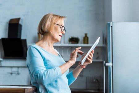 Seniorin nutzt digitales Tablet zu Hause