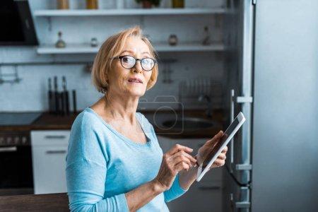 senior femme en lunettes regardant l'appareil photo et en utilisant une tablette numérique à la maison
