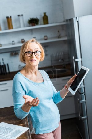 Photo for Senior woman in glasses using digital tablet and gesturing with hand in kitchen - Royalty Free Image