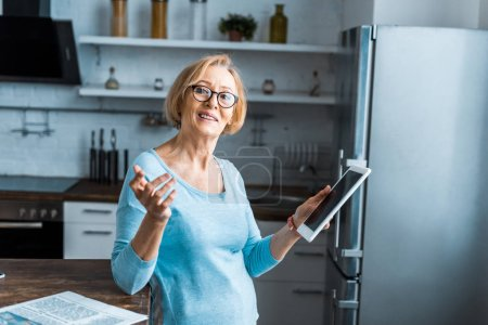 Photo for Smiling senior woman in glasses using digital tablet and gesturing with hand in kitchen - Royalty Free Image