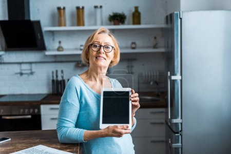 senior woman in glasses looking at camera and presenting digital tablet with blank screen in kitchen