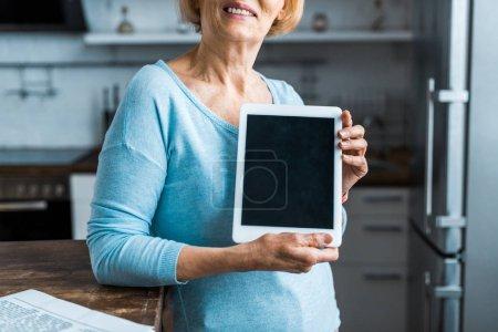 vista recortada de la mujer mayor que presenta tableta digital con pantalla en blanco en casa