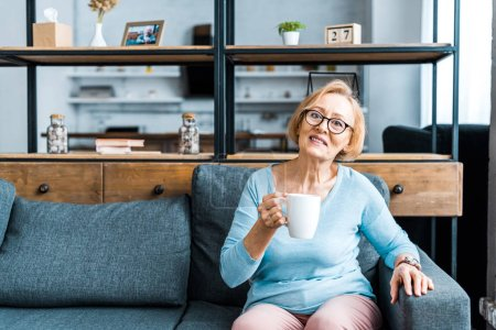 senior woman in glasses looking at camera and sitting on couch with cup of coffee in living room