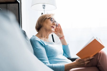 selective focus of senior woman in glasses sitting and reading book at home
