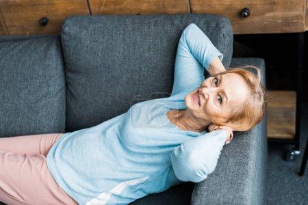 Photo pour Femme âgée souriante avec les mains sur la tête regardant la caméra, couchée et reposant sur le canapé - image libre de droit