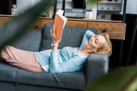 Photo pour Accent sélectif de la femme âgée couchée sur le canapé et le livre de lecture à la maison - image libre de droit
