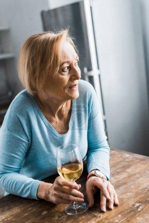 Selektiver Fokus der Seniorin, die wegschaut und zu Hause ein Weinglas hält