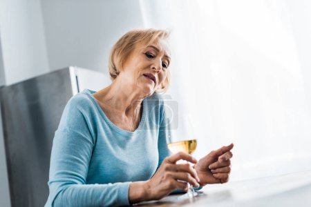 lonely senior woman in casual clothes holding wine glass at home with copy space