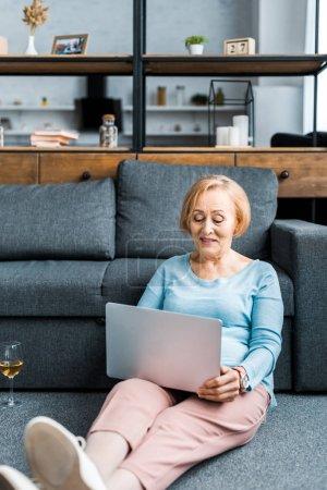 mujer mayor en ropa casual utilizando el ordenador portátil en la sala de estar