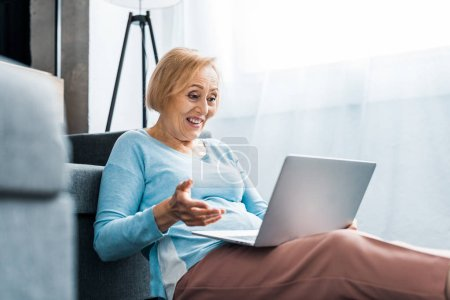 Photo for Surprised senior woman gesturing with hand while having video call on laptop at home - Royalty Free Image