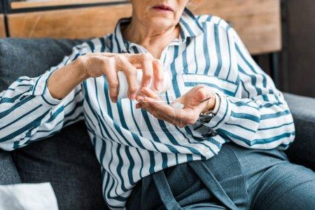 Photo pour Vue recadrée de femme senior malade assis sur le canapé et la prise de pilules à la maison - image libre de droit
