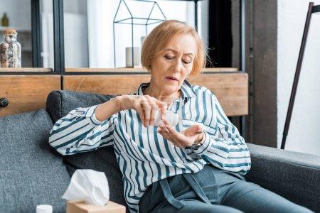 Photo pour Femme senior malade assis sur le canapé et la prise de pilules à la maison - image libre de droit