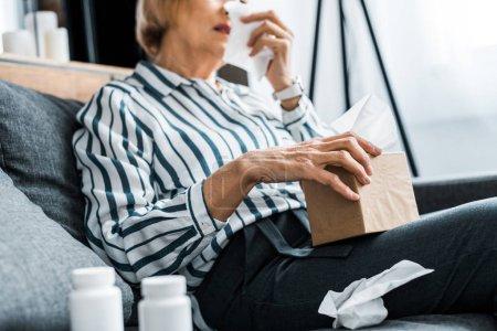 Photo pour Vue partielle de la femme senior malade avec le nez qui coule maintenant boîte de tissu à la maison - image libre de droit